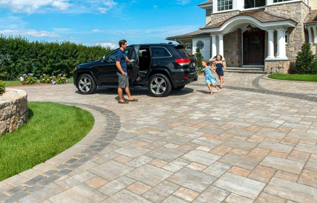 Unilock driveway and entrance with flagstone-textured Thornbury EnduraColor pavers, and heritage Courstone border