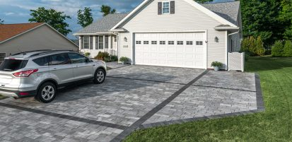 Car parked upon a contemporary Unilock Artline linear plank paver driveway, with Series border