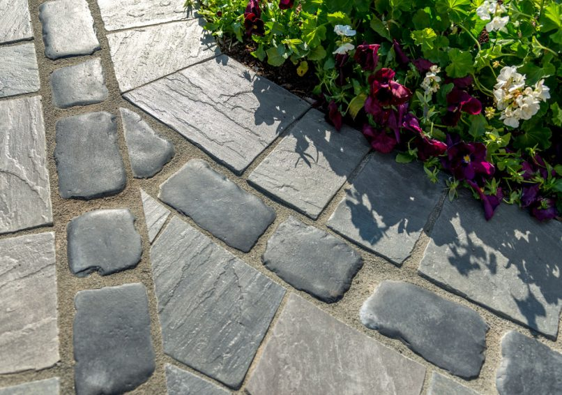Closeup of Unilock walkway with flagstone-textured Richcliff pavers and heritage Courtstone border