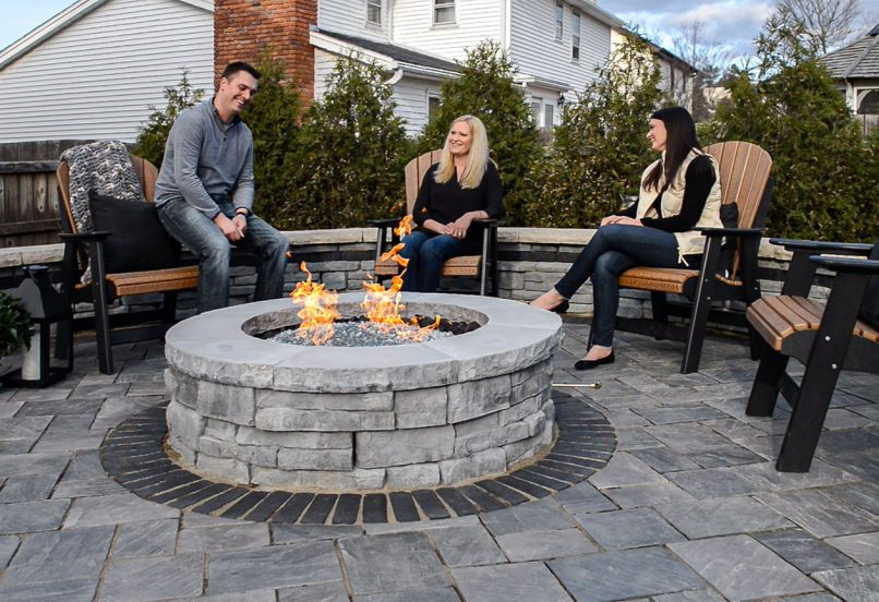 People sitting around a Unilock Rivercrest firepit, surrounded by Richcliff Elegance flagstone-textured pavers