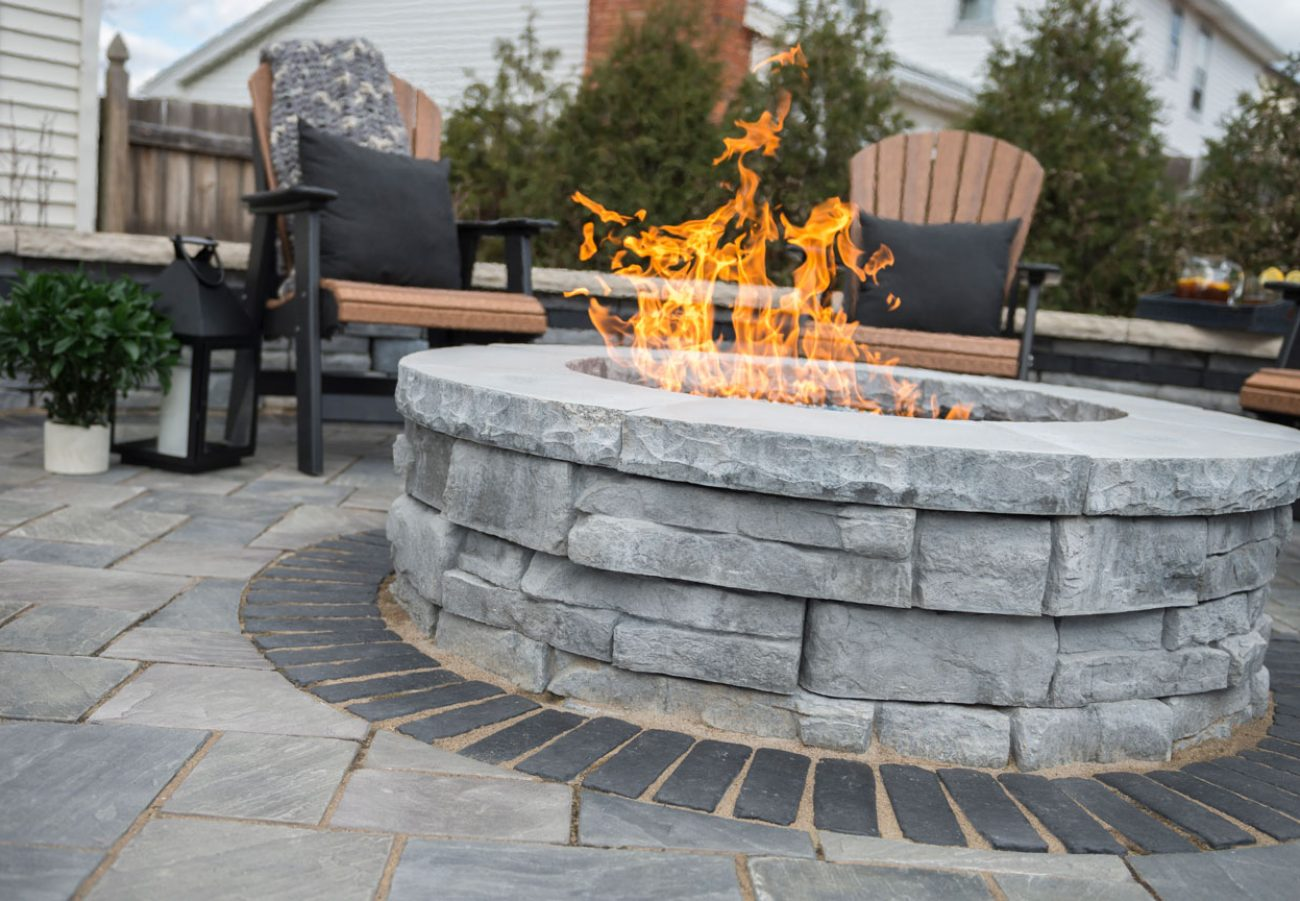 Unilock Rivercrest Wall fire feature, wall and pillars surrounded by Richcliff Elegance flagstone-textured pavers