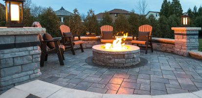 Evening scene of Unilock Rivercrest firepit, wall and pillars surrounded by Richcliff Elegance flagstone-textured pavers