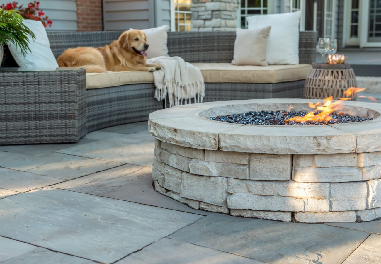 Unilock Rivercrest fire feature surrounded by Natural Stone patio
