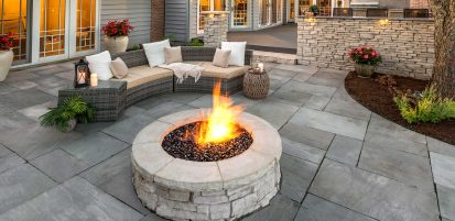Unilock Rivercrest Wall and fire feature surrounded by Natural Stone flagstone patio