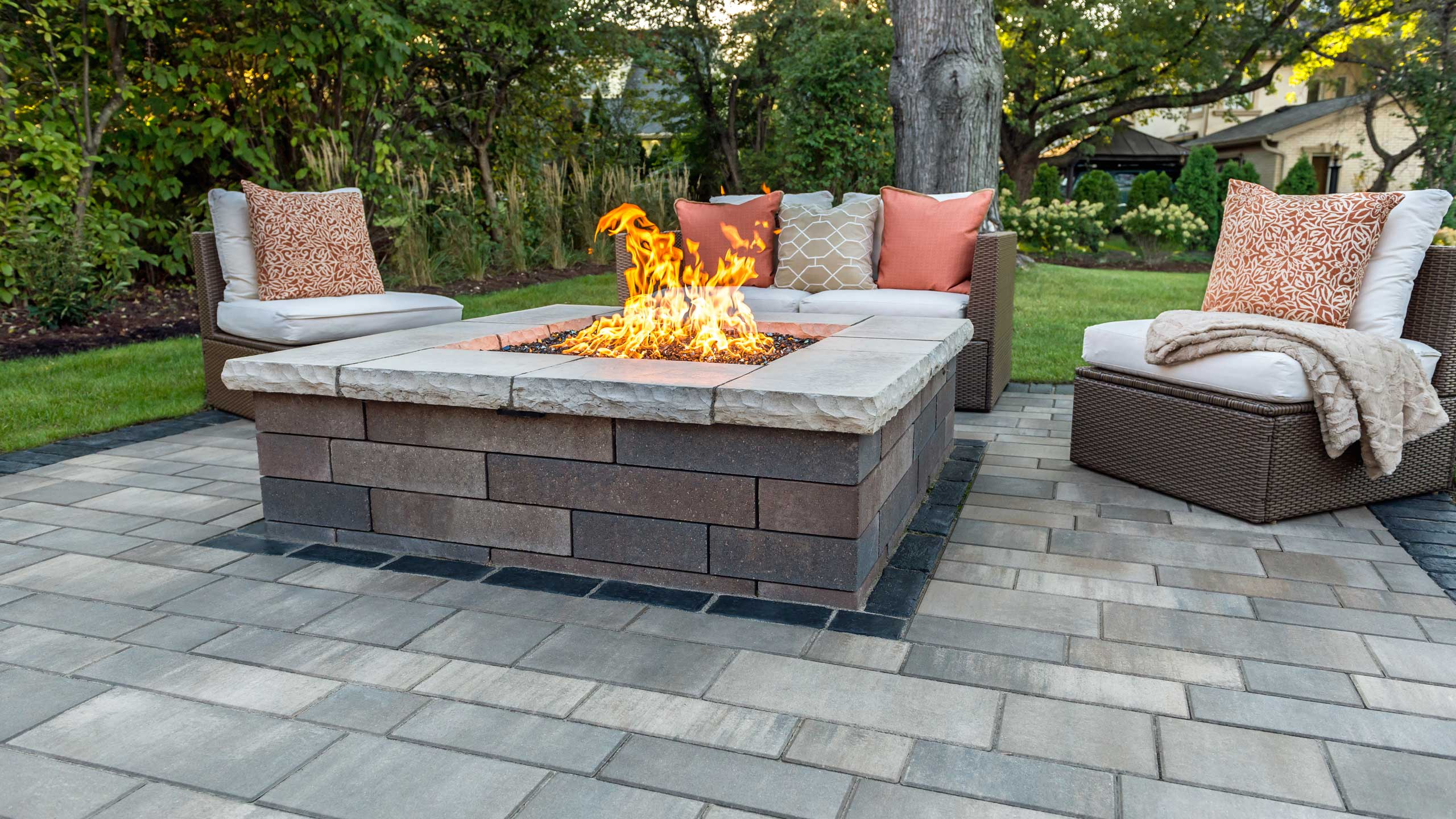 Contemporary Unilock Lineo Dimensional Stone fire feature and Artline linear plank paver patio