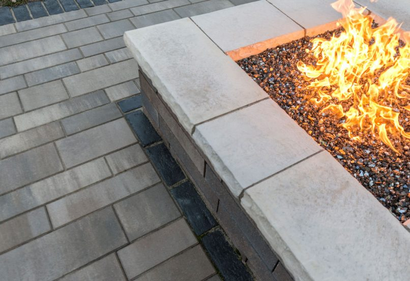 Contemporary Unilock Lineo Dimensional Stone fire feature and Artline linear plank paver patio with Town Hall Elegance border
