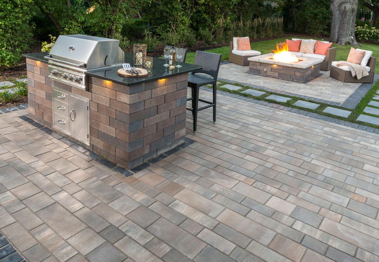 Contemporary Unilock Lineo Dimensional Stone outdoor kitchen and fire feature, with Artline linear plank paver patio