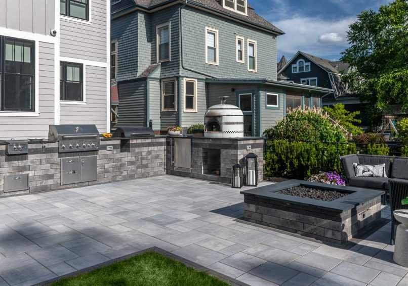 Unilock Lineo Dimensional Stone outdoor kitchen and fire feature, surrounded by Beacon Hill Smooth EnduraColor pavers