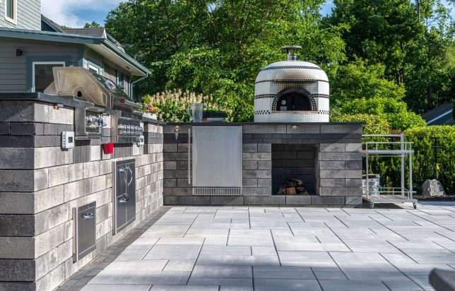Unilock Lineo Dimensional Stone outdoor kitchen surrounded by Beacon Hill Smooth EnduraColor pavers