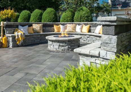 Outdoor seat wall and firepit built with Unilock Rivercrest Wall, surrounded by contemporary Umbriano pavers