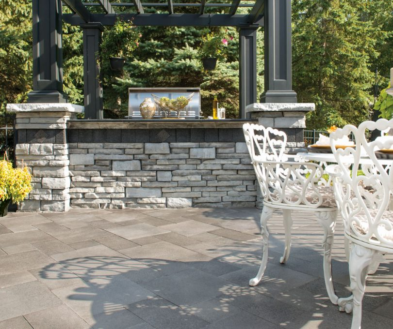 Outdoor Kitchen built with Unilock Rivercrest Wall, surrounded by contemporary Umbriano pavers