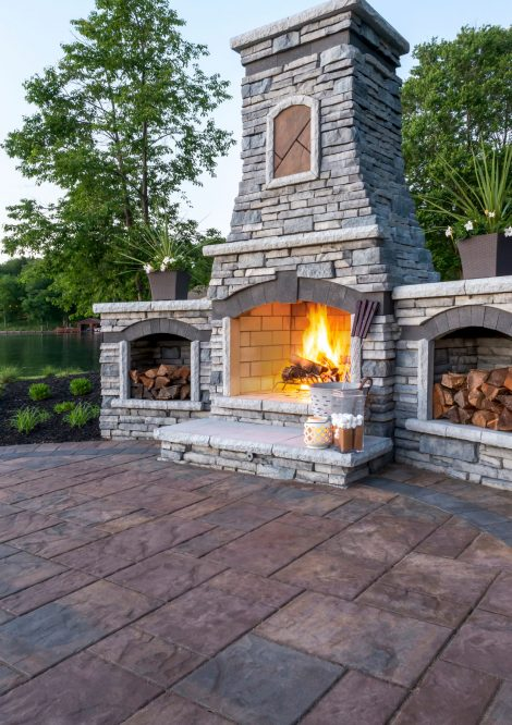 Unilock Outdoor living space with Beacon Hill Flagstone paver patio and custom Rivercrest fire feature