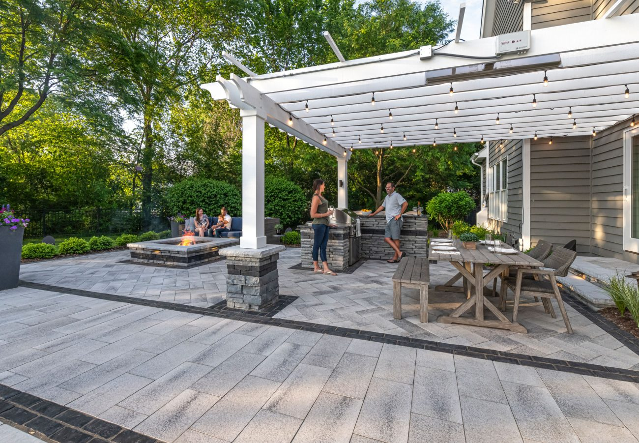 Unilock Outdoor living space with Rivercrest fire feature, outdoor kitchen surrounded by Umbriano paver patio