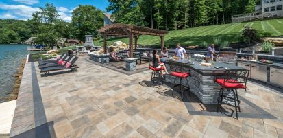 Unilock Outdoor living space with Beacon Hill Flagstone paver patio and Rivercrest fire feature and grill island