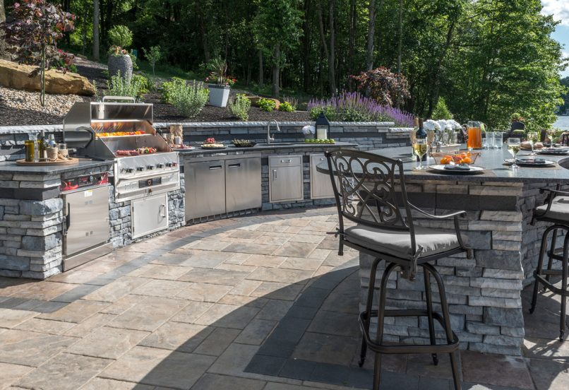 Unilock Outdoor kitchen with Beacon Hill Flagstone paver patio and Rivercrest grill island