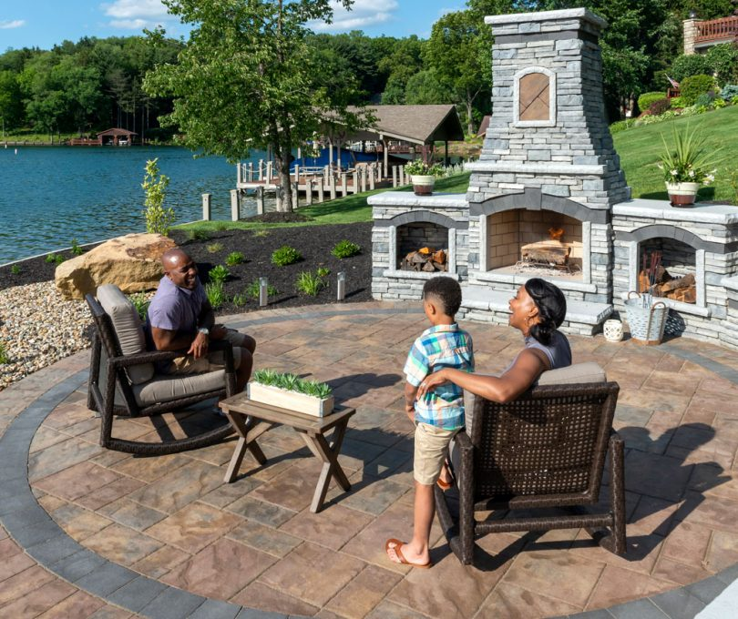 Unilock Outdoor living space with Beacon Hill Flagstone paver patio and custom Rivercrest fireplace