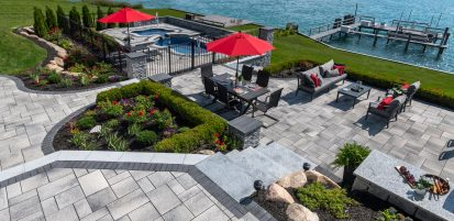 Unilock Outdoor living space with Umbriano Pool Deck and Rivercrest Wall pillars and outdoor kitchen