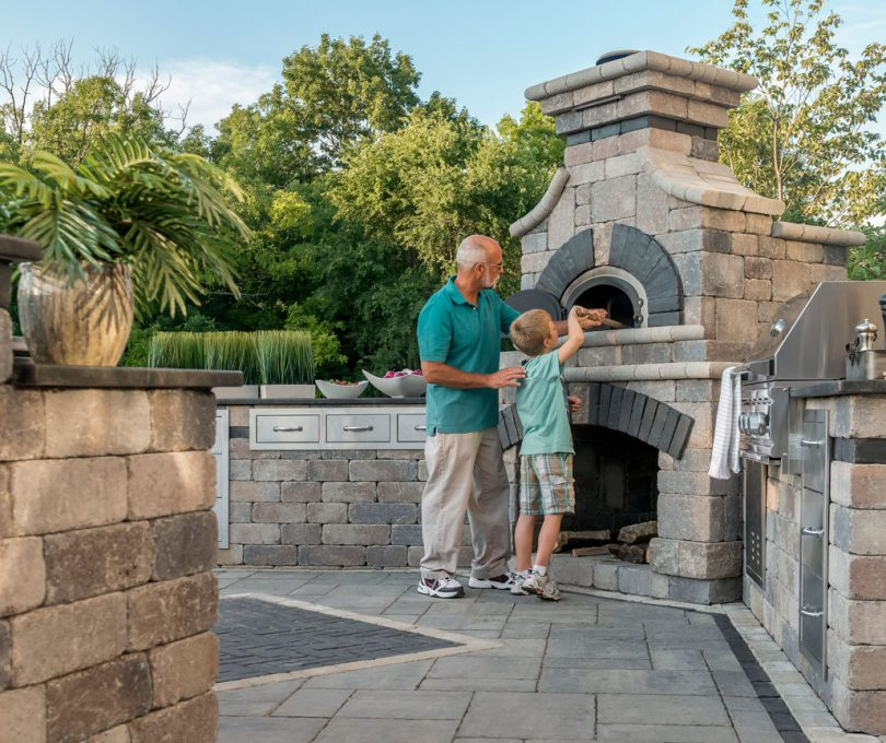 Unilock Outdoor Kitchen with people cooking at Olde Quarry grill island and pizza oven, standing on Bristol Valley pavers