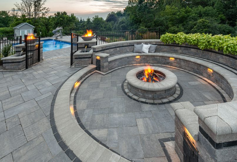 Unilock Olde Quarry fire feature and surrounding seat wall with Bristol Valley pool deck in background