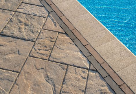 Closeup of Unilock Beacon Hill Smooth pool deck, with anqitued Mattoni border