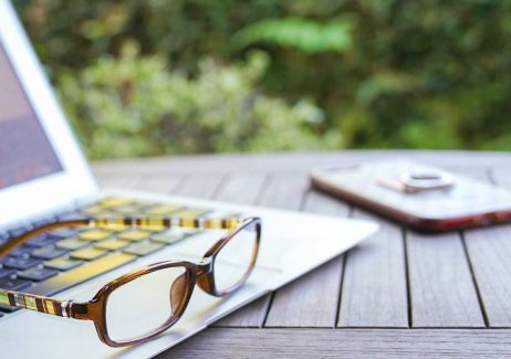 Closeup of reading glasses on a laptop, sitting upon a wooden patio table