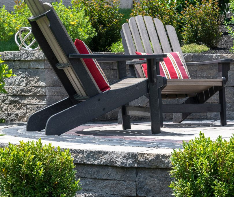 Close up of two chairs on a Unilock paver patio backed by Estate Wall garden retaining wall