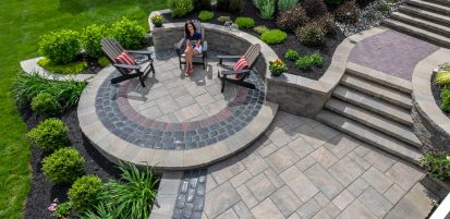 Woman sitting in chair reading tablet upon a Unilock Beacon Hill flagstone patio, with Coutrstone and Copthorne accents