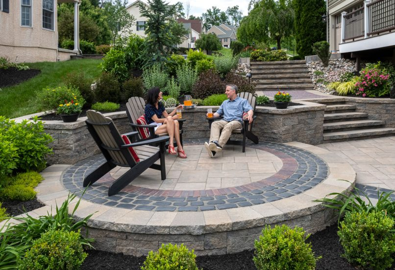 Couple sitting in patio chairs placed on a Unilock Beacon Hill flagstone paver patio, with Coutrstone and Copthorne accents