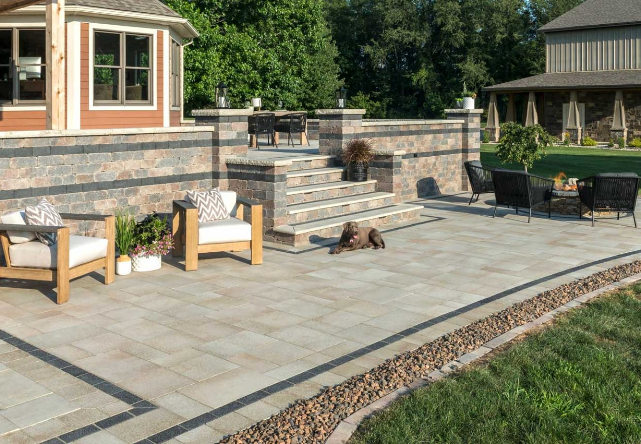 Unilock EnduraColor Outdoor living space with contemporary Umbriano pavers and antiqured Olde Quarry retaining wall and steps