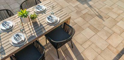 Dinner table setup upon Unilock contemporary Umbriano EnduraColor paver patio