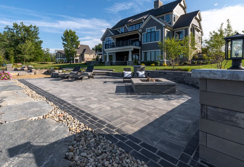 Unilock Beacon Hill Smooth paver patio with Town Hall Elegance paver border and U-Cara seat wall and fire feature