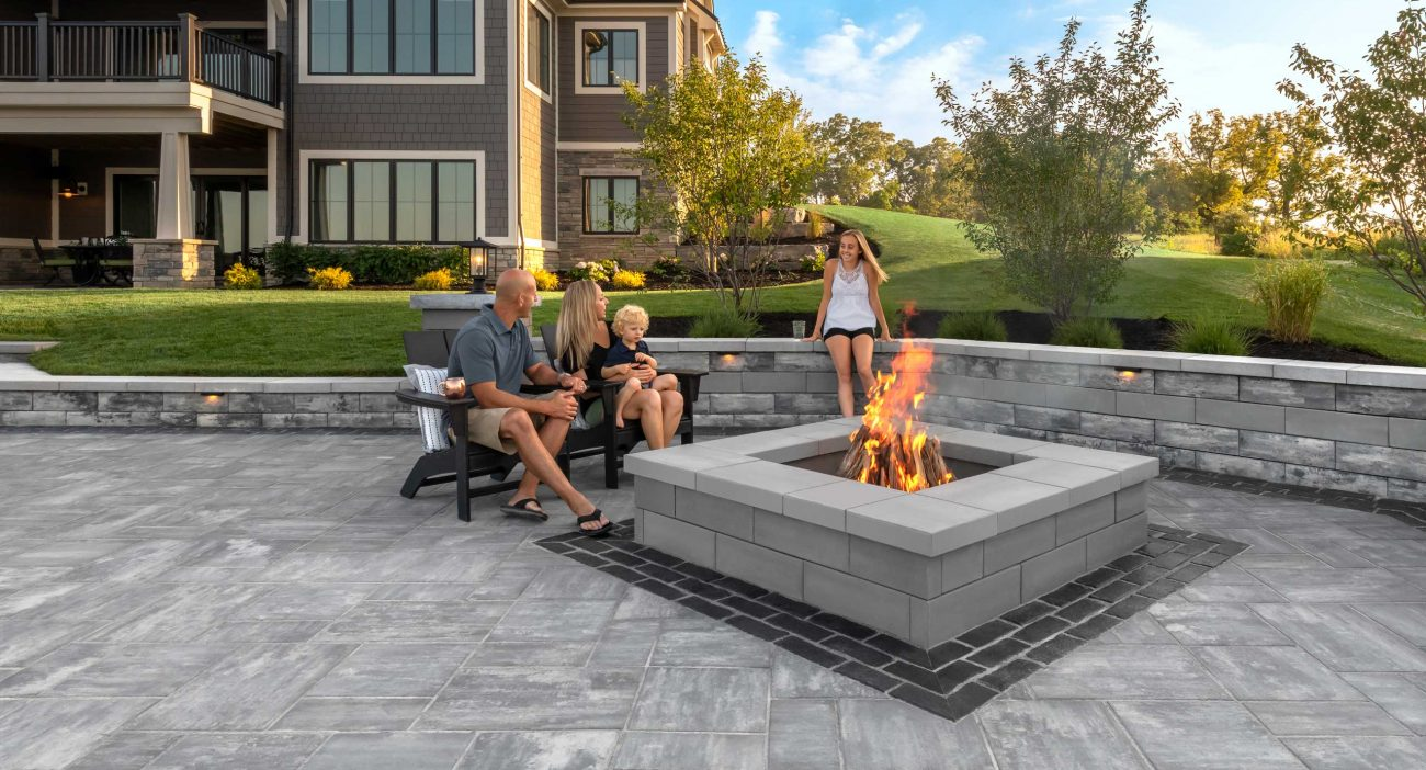 Family sitting together on chairs and Unilock U-Cara seat wall enjoying their U-Cara firepit