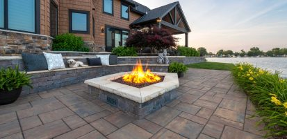 Unilock Brussels Dimensional seatwall and firepit surrounded by Beacon Hill Flagstone pavers overlooking waterway