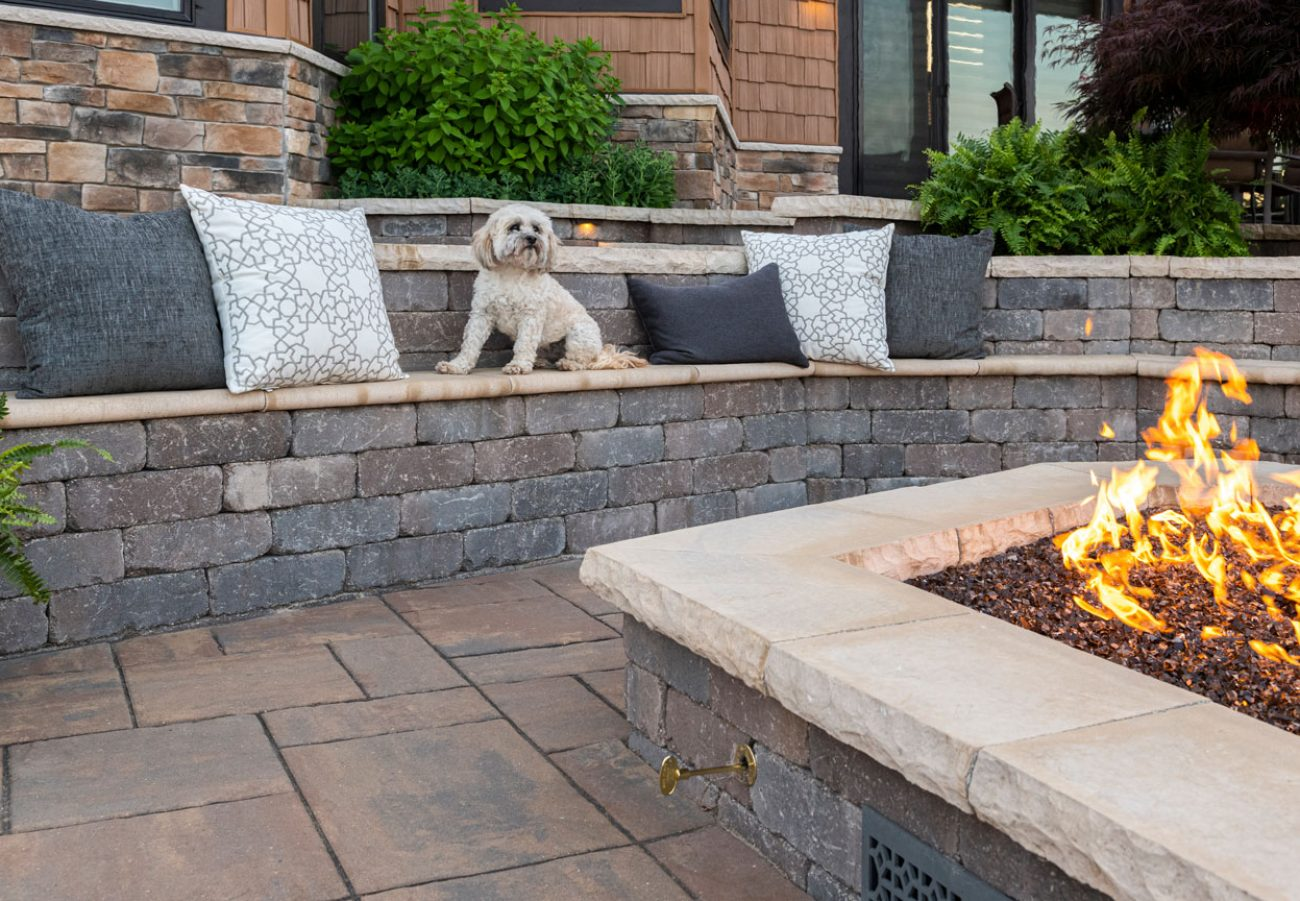 Small white dog sitting onUnilock Brussels Dimensional seatwall enjoying firepit surrounded by Beacon Hill Flagstone pavers