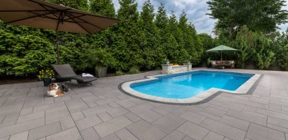 Unilock contemporary Umbriano pool deck with fire feature