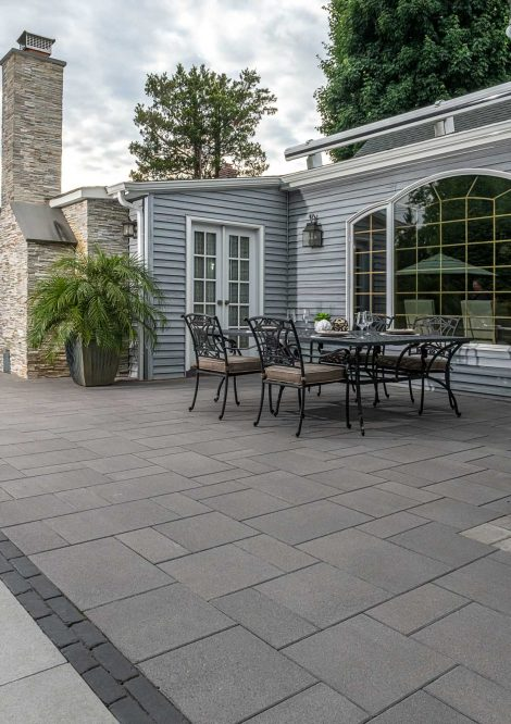 Contemporary Unilock Umbriano patio with dining table and chairs