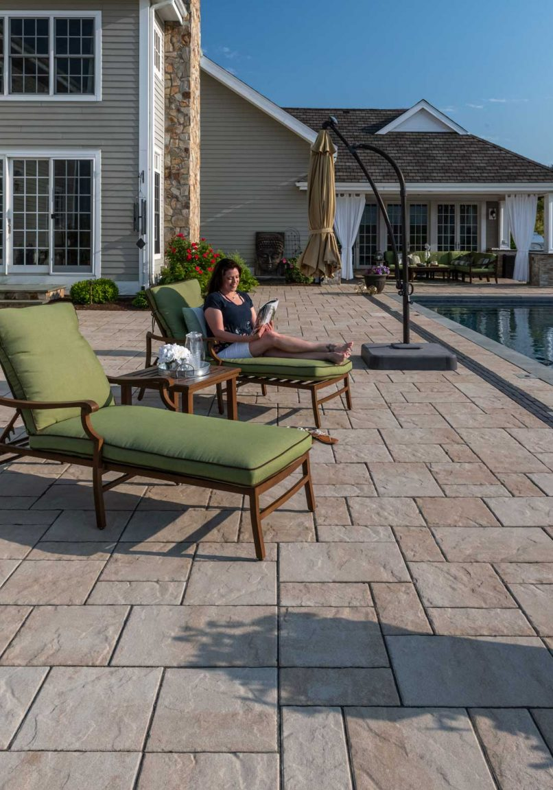 Woman in lounge chair reading a book on a Unilock Beacon Hill Flagstone EnduraColor pool deck