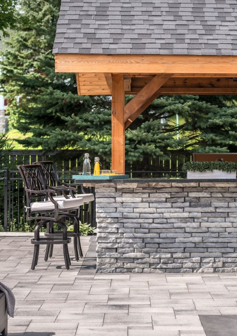 Unilock Umbriano pavers surrounding outdoor kitchen made of Rivercrest Wall