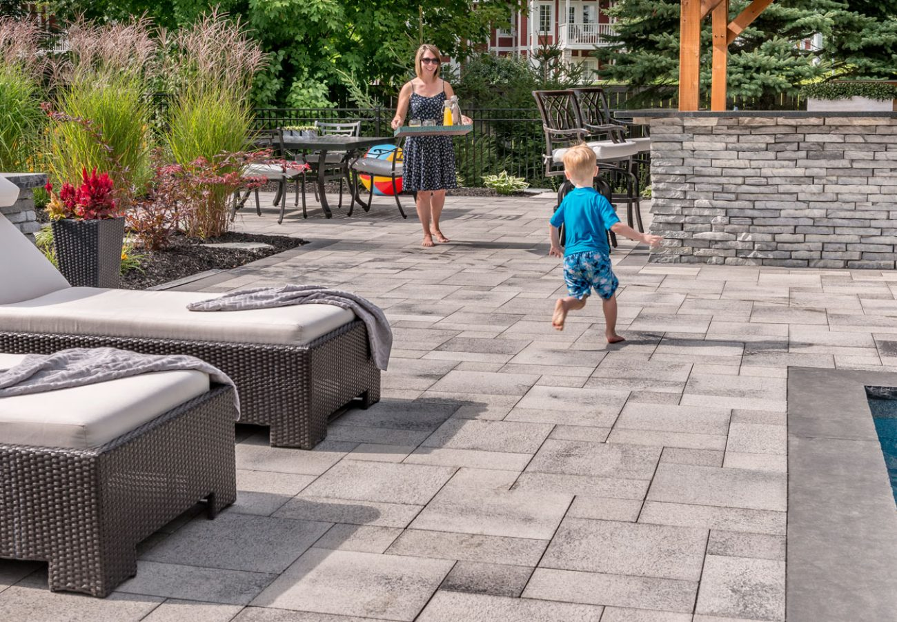 People enjoying outdoor living space made of Unilock Umbriano pavers surrounding Rivercrest Wall outdoor kitchen