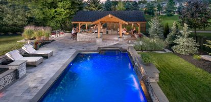 Evening scene of Unilock Umbriano EnduraColor paver pool deck and Rivercrest Wall water feature and outdoor kitchen