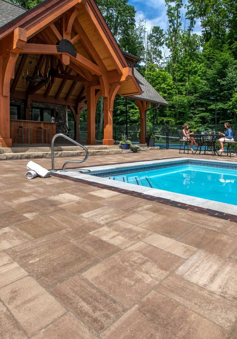 Unilock Bristol Valley paver pool deck with Copthorne Elegance paver accents, two people sitting nearby at café table