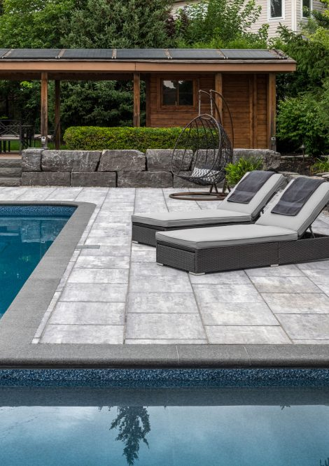 Lounge chairs upon a contemporary pool deck using Unilock large format Beacon Hill Smooth slab pavers