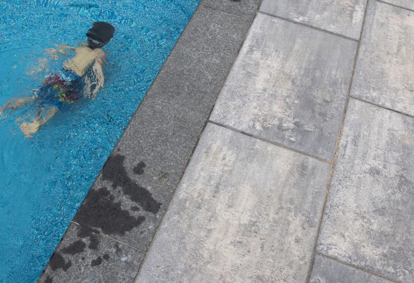Unilock Beacon Hill smooth pool deck, little boy swimming