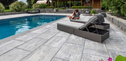 Little boy and woman playing on contemporary Unilock Beacon Hill Smooth slab paver pool deck