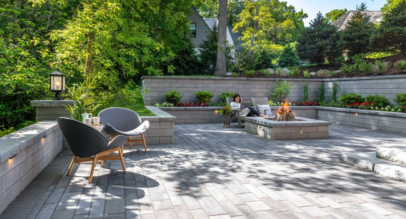 Unilock U-Cara retaining wall, fire feature and seat wall planter with Artline contemporary plank pavers