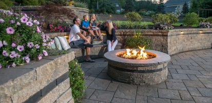 Family gathered around Estate Wall fire feature, surrounded by Beacon Hill Flagstone pavers