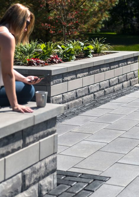 Contemporary outdoor living space with Unilock EnduraColor Umbriano pavers and woman sitting on U-Cara seat wall