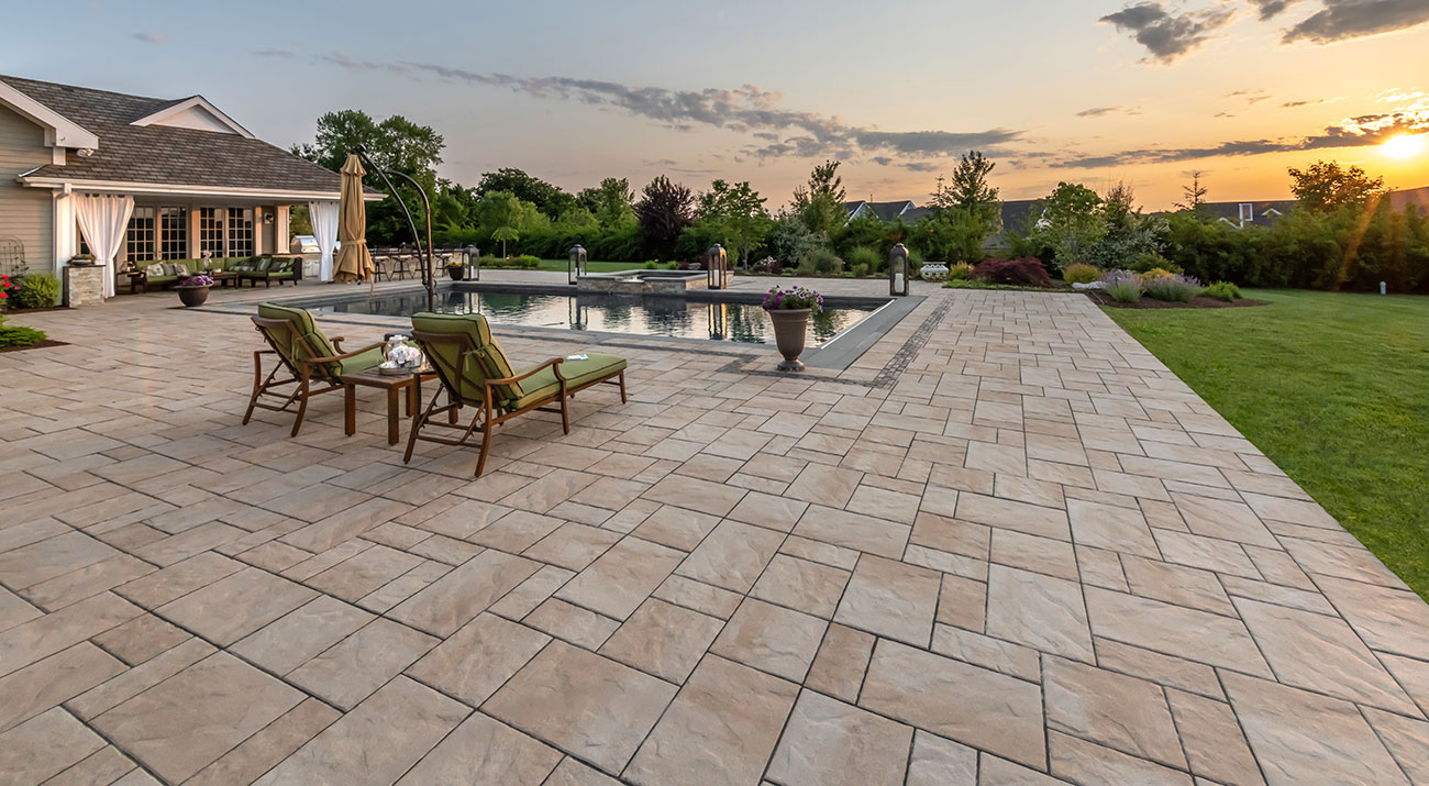 Lounge chairs sitting upon a Unilock Beacon Hill Flagstone paver pool deck with Copthorne accent, with sun setting