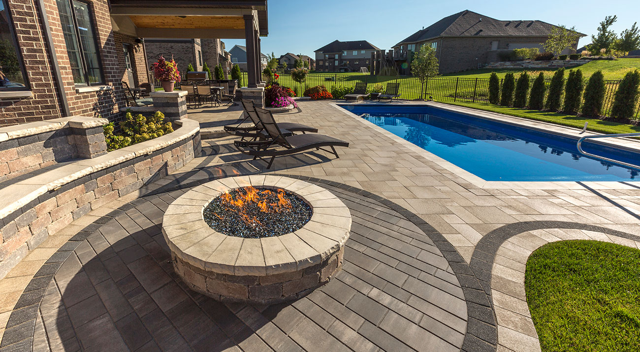 Unilock antiqued fire feature surrounded by contemporary linear plank pavers