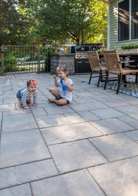 Kids making bubbles on the Unilock Patio with Beacon Hill Flagstone